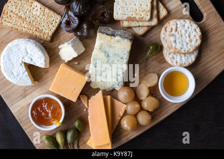 Cheese board serving with figs, caper berries, jam, honey and pickled onions. Top view photograph with copy space - Stock Photo