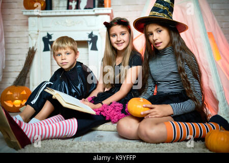 Smiling pretty children in costumes sitting on floor near teepee and looking at camera while reading Halloween stories - Stock Photo