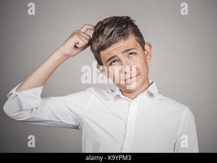 Closeup portrait young man scratching head, thinking daydreaming deeply about something, looking up, isolated grey - Stock Photo