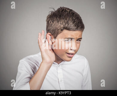 Closeup portrait unhappy hard of hearing man placing hand on ear asking someone speak up, listening to bad news - Stock Photo