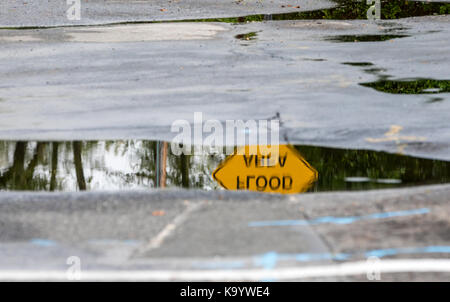 a flood area warning sign in the reflection of a water puddle, sag harbor, ny - Stock Photo
