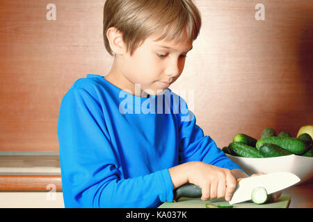 Little boy cutting vegetables in the kitchen - Stock Photo