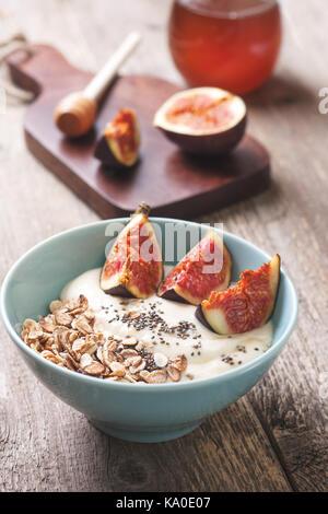 healthy breakfast. muesli, yoghurt, figs, chia seeds in a blue bowl ha old wooden background - Stock Photo