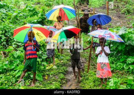 Native women with children with colourful umbrellas in the rain in the village of Rangsuksuk, island of Pentecost, - Stock Photo