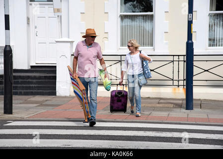 Holidaymakers using Zebra crossing to cross a road safely. - Stock Photo