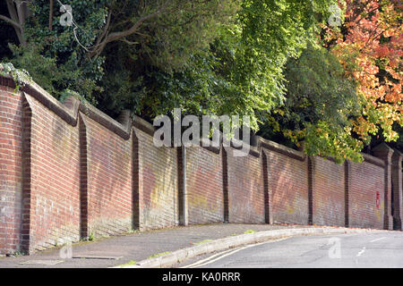 A brick wall on a hilll and a corner in caterham, surrey,  with autumn trees hanging over the top. - Stock Photo