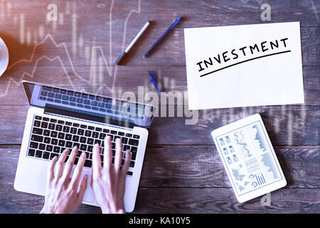 Investment concept with business person typing on computer and financial dashboard on digital tablet, top view wooden - Stock Photo