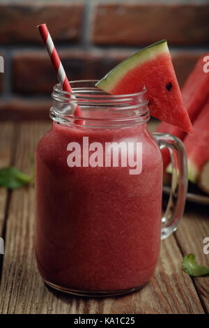 Freshly made smoothies from pieces of watermelon and a banana in a glass jar on a wooden table - Stock Photo