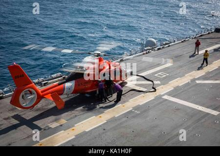 Coast Guard Cutter Forward's embarked HITRON MH-65 Dolphin Helicopter receives fuel from amphibious assault ship - Stock Photo