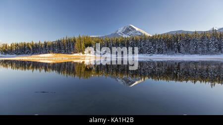 Distant Snowy Mountain Top Reflection and Landscape Panorama after early Autumn Snowfall in Foothills of Rocky Mountains - Stock Photo