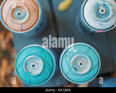 Spray paint dispenser in different colors. Top view on graffiti bottles of aerosol. - Stock Photo