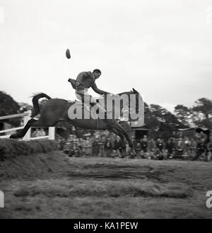 1950s, historical, outdoor eventing competition, a male rider on his horse jumping over a water fence holding the - Stock Photo