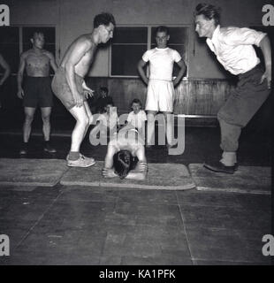1950s, historical picture showing the inside of a gym and two men leaping over a youngster's bare back who is crouched - Stock Photo