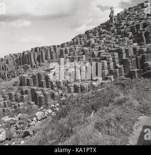 1950s, historical, a gentleman stands on top of the ancient volcanic rock basalt columns at the unique Giant's Causeway, - Stock Photo