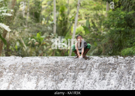 Children from small village under Mount Agung playing in watterfall - Stock Photo