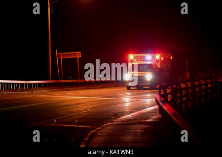 Speculator, NY ambulance racing to a medical emergency at night. - Stock Photo