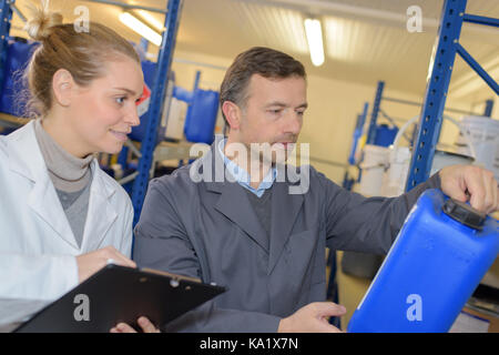 man and co-worker examining air compressor in hardware store - Stock Photo