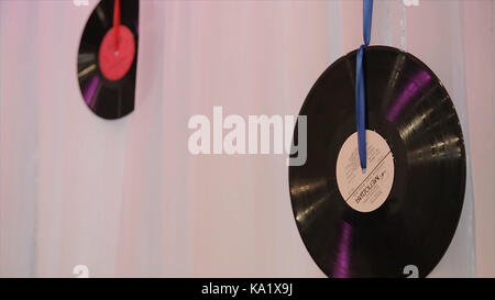 vinyl records hang on the wall with red ribbons. Black vinyl records.Using vinil records like a element of decor - Stock Photo