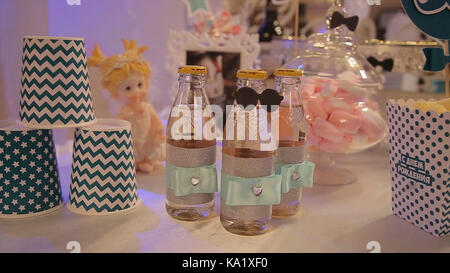 different bottles of juice on the table. Bottled drinks for guests at the party. glass bottles with drinks. Bottles - Stock Photo