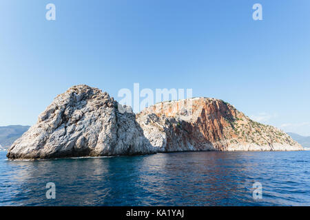 Seascape with Alanya's castle rock peninsula and mountains as backgroung shot on sunny day - Stock Photo