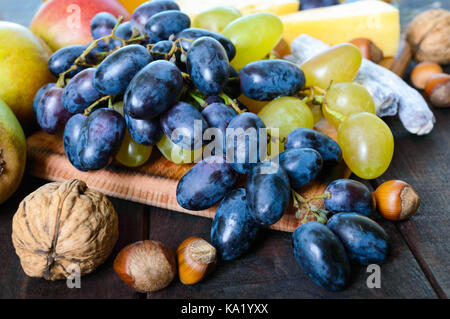 Autumn set of products: grapes, walnuts, hazelnuts, plums, honey, cheese, raisins, pears, dried cranberries on a - Stock Photo