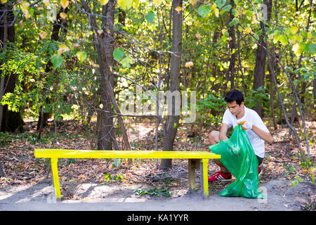 Sofia, Bulgaria - 16 September, 2017: Young man picks up trash in the forest participating in a cleaning campaign. - Stock Photo