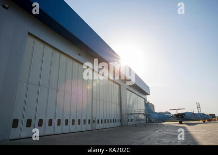 Airport hangar from the outside with big tall doors. Bright blue sky with sunlight. - Stock Photo