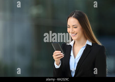 Single smiley executive woman using a mobile phone walking on the street - Stock Photo