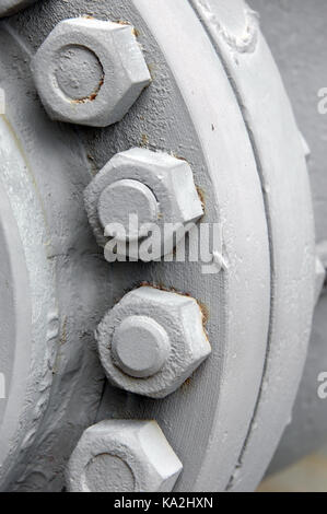 Closeup of industrial detail shows cylinder of steel wheel with exposed nuts and bolts. - Stock Photo