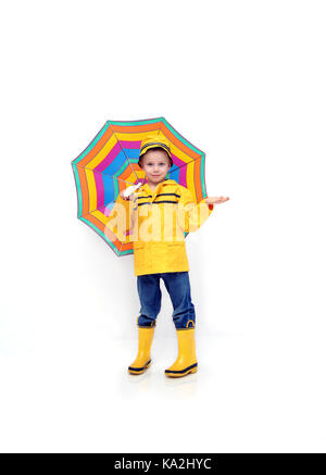 Little boy checks for rain while dressed in a yellow slicker and rubber boots and hat.  He is holding a multi-striped - Stock Photo