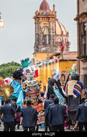 A marching band follows a parade of giant paper-mache puppets called mojigangas in a procession through the city - Stock Photo