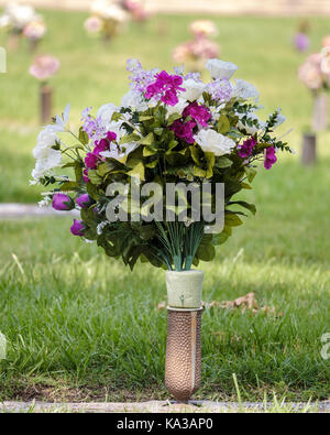 Gravesite floral decorations honoring the dead on Memorial Day in a cemetary in Wichita, Kansas, USA. Closeup of - Stock Photo