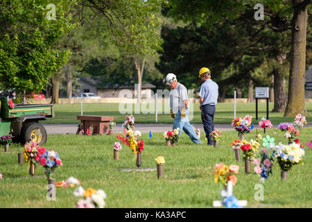Two cemetery employees walk among floral decorations honoring the dead on Memorial Day in a cemetary in Wichita, - Stock Photo