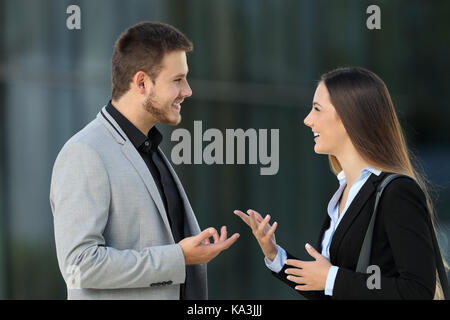 Side view portrait of a happy couple of executives talking on the street - Stock Photo