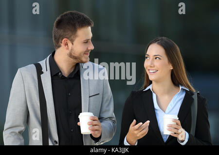 Front view of a happy couple of executives walking and talking on the street with an office building in the background Stock Photo