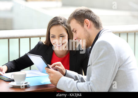 Two executives consulting on line data in a tablet sitting in a restaurant terrace - Stock Photo