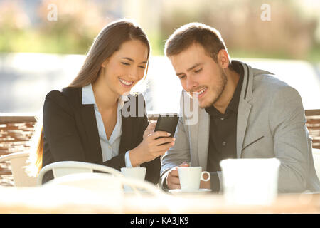 Two happy executives using a smart phone sitting in a restaurant terrace with a warm light in the background - Stock Photo