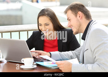 Two executives working on line with a laptop sitting in a bar terrace - Stock Photo