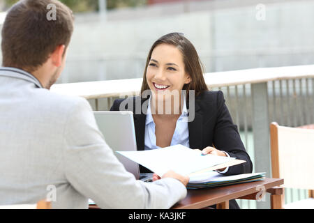 Two executives working sharing informs sitting in a bar terrace - Stock Photo