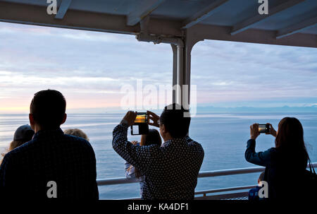People passengers taking photos with their iphones and mobile phones from a BC ferry ship deck traveling on the - Stock Photo