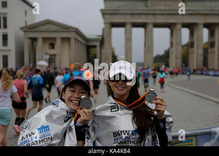 Berlin, Germany. 24th Sep, 2017. Two runners pose with their medals in front of the Brandenburg Gate. More than - Stock Photo