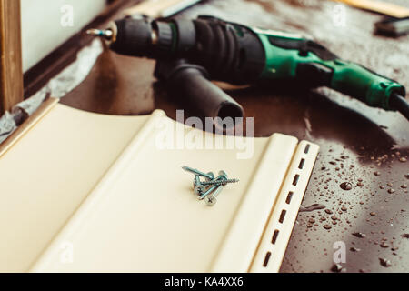 Screws lie next to the electric screwdriver on the windowsill - Stock Photo