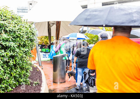 Washington DC, USA - September 2, 2017: People waiting in line queue holding umbrellas during heavy pouring, downpour - Stock Photo