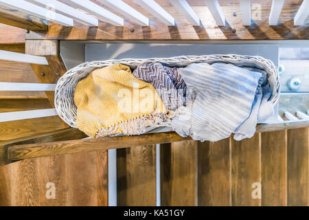Closeup of laundry or linen wooven basket filled with warm blankets by stairs indoors in staging model house, home, - Stock Photo
