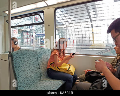 BERLIN, GERMANY- AUGUST 26; young woman while traveling on city train smiling while using mobile device on August - Stock Photo