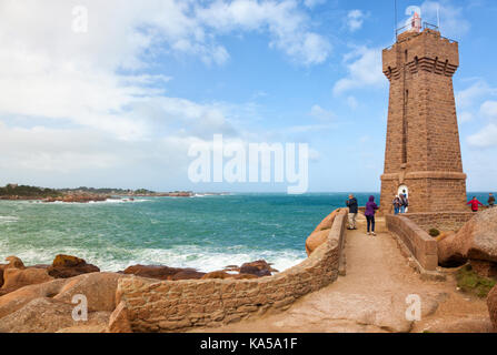 People visiting the lighthouse of Ploumanac'h at the french Côte de granite rose in Brittany - Stock Photo