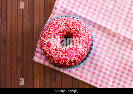 Brightly pink donut on a brown wooden background. With pink checkered cloth - Stock Photo