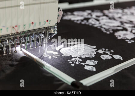 Sewing machine in work, textile fabric, nobody. Factory production, sew manufacturing, needlework technology - Stock Photo