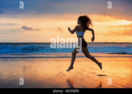 Barefoot girl silhouette running along ocean surf by water pool to keep fit, health. Sunset beach background with - Stock Photo