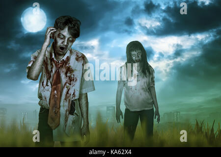 Scary two asian zombies with wound and mad expression on the night - Stock Photo